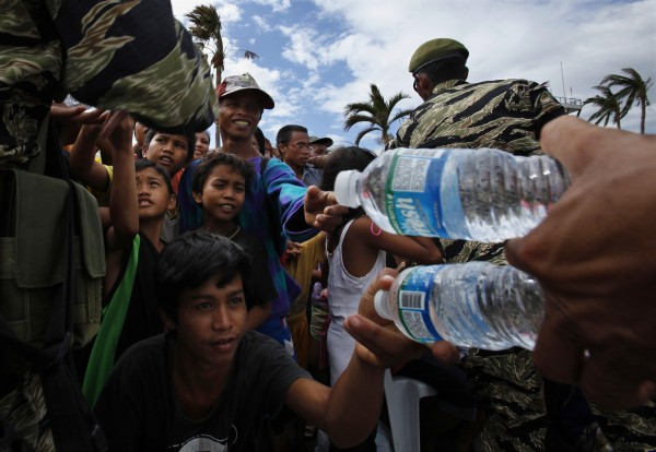 Filipino soldiers distribute drinking water to residents affected by Typhoon Haiyan at Tacloban airport on Nov. 16, 2013.