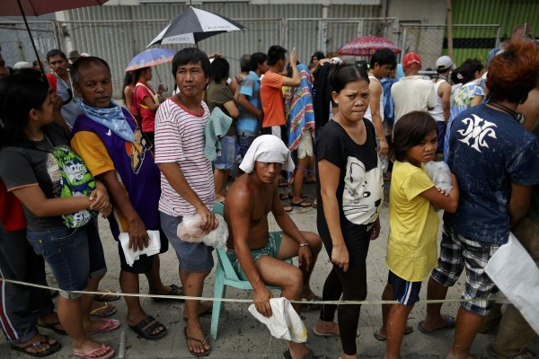 Survivors wait in line for aid to be distributed in Tacloban on Nov. 16, 2013.