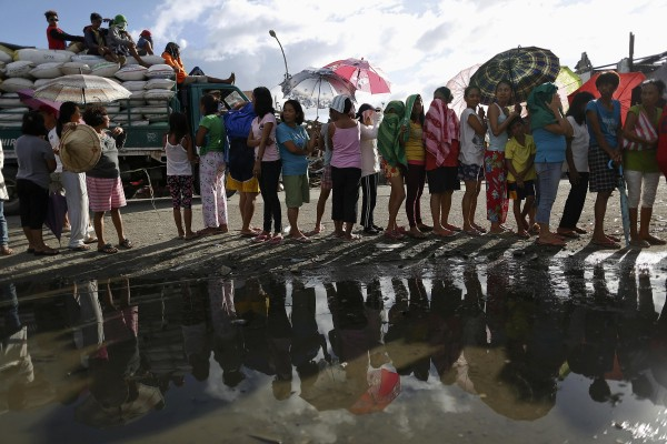 Survivors wait in line for aid to be distributed in an area devastated by Typhoon Haiyan, south of Tacloban on Nov. 16, 2013.