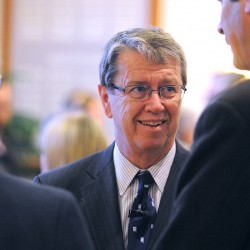 Dr. David Bronson, a University of Maine graduate and president of the Cleveland Clinic Regional Hospitals, talks with people before his lecture in Orono on Wednesday.
