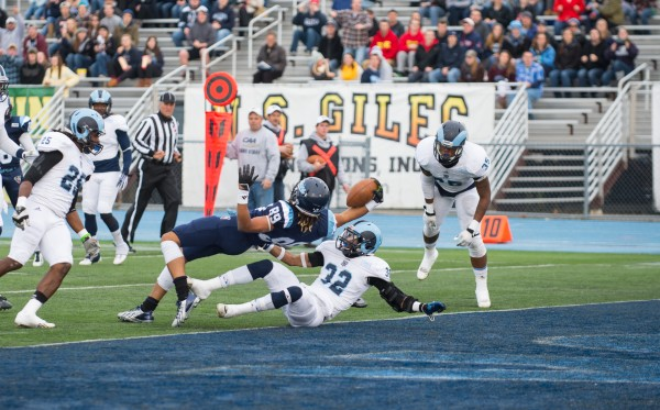 The University of Maine's Arthur Williams dives backward into the end zone for a touchdown at Alfond Stadium in Orono Saturday. The University of Maine won 41-0 and are CAA football champions.