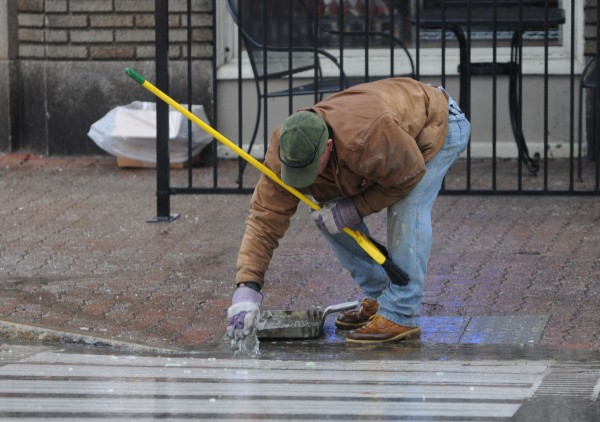Building maintenance man Geno McLaughlin picks glass from the crosswalk on Hammond street after wind pulled the glass from a third-story business and sent it dashing to the sidewalk below. No was one injured when the glass fell.