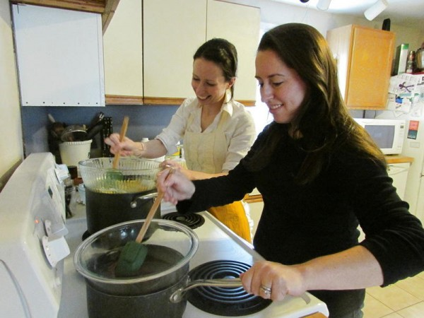 Ashley O'Neil, left, stirs a lip balm mixture, while her sister Lindsay Crawford stirs a cheek and lip tint made from red beet powder and vegetable glycerin. Their home-based Yarmouth business, Herbal Grace Creations, produces natural skin- and personal-care products.