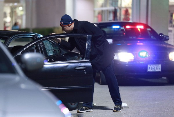 A detective investigates the scene of a police-involved shooting outside Kohl's department store on Weber Road in Romeoville, Ill., Nov. 28, 2013. A theft attempt by two or more suspects resulted in police action and the shooting scene outside the store.