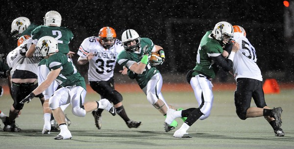 Snow falls on the field as Seth Adams breaks through the line for a gain in the second half of the Class C Championship game Saturday in Portland.  The Hornets won 47-18.