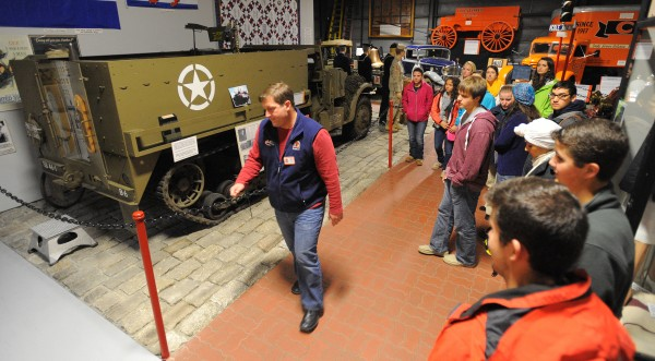 Jim Neville, director of operations (center), leads a group of University of Maine students through the Cole Land Transportation Museum in Bangor Sunday, Nov. 10, 2013. Galen Cole, a World War II veteran, spoke with students about his war experience and treated them to lunch. The group presented Cole with a UMaine jacket and thanked him for his service to the country.