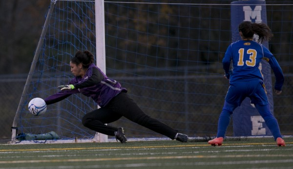 Richmond's goalie Kelsie Obie makes a save on a shot by Washburn's Laina Mette  in the Class D soccer state championship, Saturday, Nov. 9, 2013, in Bath, Maine.