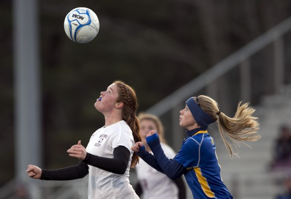 Richmond's Kalah Patterson, left, and Washburn's Mackenzie Worcester go for the ball at midfield in the Class D soccer state championship, Saturday, Nov. 9, 2013, in Bath, Maine.