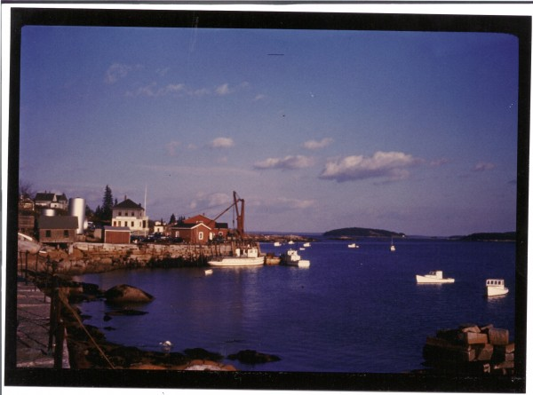 A photograph shows Stonington in the 1960s, while the memorial for JFK was being cut in this town. The Deer Island Granite company, which recieved the commission to cut the granite, had an office in the two story building. The boat tied to the peer was used to ferry stone cutters back and forth to Crotch Island, where the quarry was.