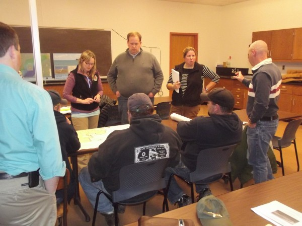 Navy and state officials gathered around a table to discuss a nautical chart with fishermen during a meeting at the University of Maine Machias Tuesday evening, Nov. 19. Navy officials briefed the fishermen on plans to bury a power cable under Machias Bay.
