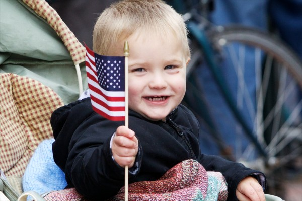 Braydon Hawkes, 1, of Westbrook welcomes parade marchers with a flag and a smile during Veterans Day observances in Portland on Monday.