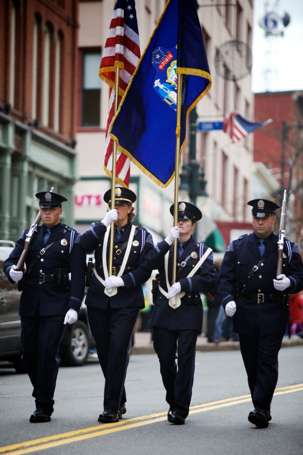 A Portland Police Department color guard makes its way down Congress Street to applause from those on the parade route Monday morning during Veterans Day observances.