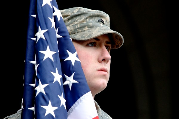 A University of Southern Maine ROTC color guard cadet stands on the steps of city hall in Portland Monday during Veterans Day observances.