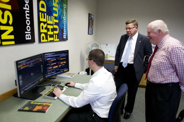 From left, MBA student Adam Bates, Dean of the Business School Ivan Manev and Professor of Finance Robert Strong show the Bloomberg terminal in a computer lab at University of Maine Orono.