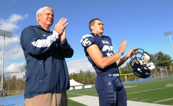 Outgoing University of Maine athletic director Steve Abbott and punter Jeffrey Ondish applaud the Black Bears football team as it advances the ball against Stony Brook on Nov. 2 at Alfond Stadium.