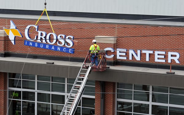 Bangor Neon crews hang the Cross Insurance Center signs on the new Banogr auditorium and civic center in May.