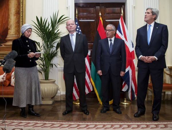 An interpreter, left, speaks during a news conference with U.S. Secretary of State John Kerry, right, Libyan Prime Minister Ali Zeidan, center, and British Foreign Secretary William Hague, at Winfield House, the residence of the U.S. Ambassador to Britain, in London, Nov. 24, 2013. Kerry arrived in London on Sunday to meet British and Libyan officials after taking part in breakthrough talks curbing Iran's nuclear activity.