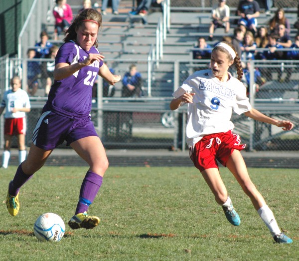 Hampden Academy's Erin Jeter (27) prepares to send a pass ahead of oncoming Mount Ararat midfielder Christine Levesque during an Eastern Maine Class A high school soccer semifinal in Topsham on Saturday. No. 2 Mount Ararat beat No. 3 Hampden 2-1.