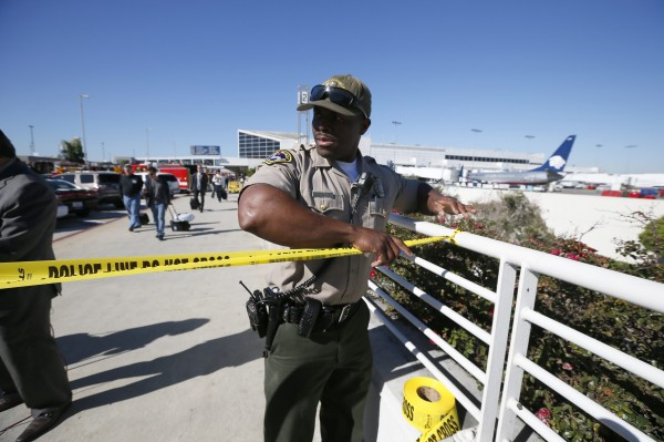 An airport police officer cordons off Terminals 2 and 3 after a shooting at Los Angeles airport , Nov. 1, 2013. A suspect in a multiple-victim shooting incident at Los Angeles International Airport has been taken into custody and is the only suspect in the incident, a Los Angeles police spokeswoman said Friday.