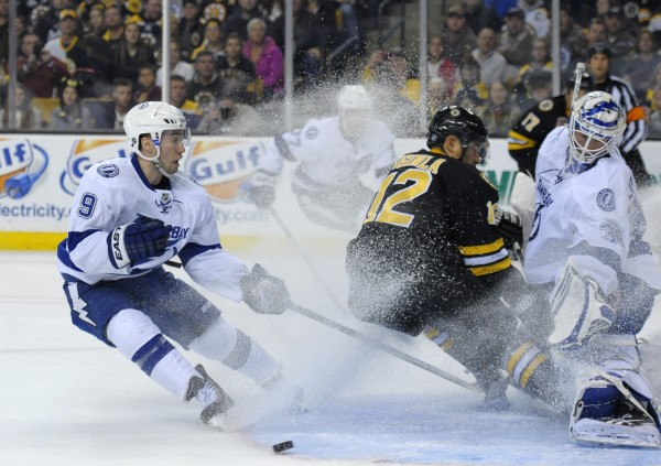 Boston Bruins right wing Jarome Iginla (12) collides into Tampa Bay Lightning goalie Anders Lindback (39) and has his goal disallowed while Lightning center Tyler Johnson (9) defends during the third period at TD Banknorth Garden in Boston Monday.