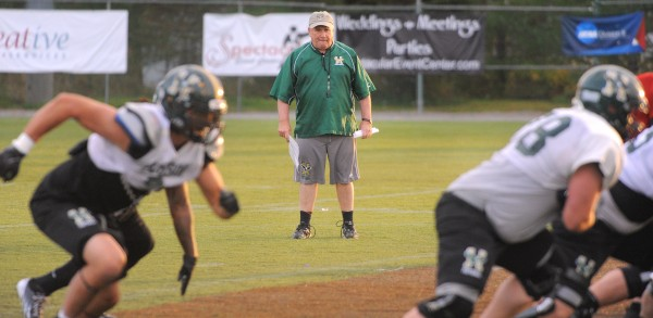 Husson University football head coach Gabby Price looks at a play during an October practice in Bangor.