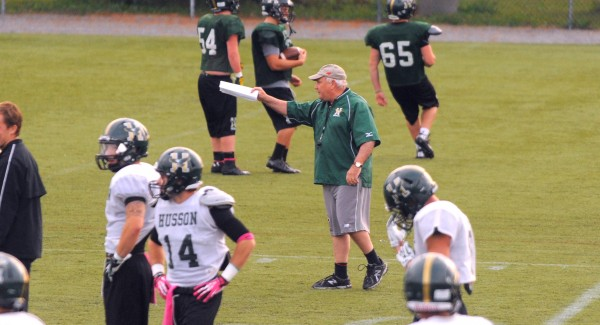 Husson University football head coach Gabby Price talks to players during an October practice in Bangor.