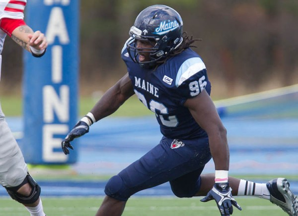 Senior defensive end Erwin Roach of the University of Maine (right) pressures Stony Brook quarterback Lyle Negron during their Nov. 2 game at Alfond Stadium in Orono.