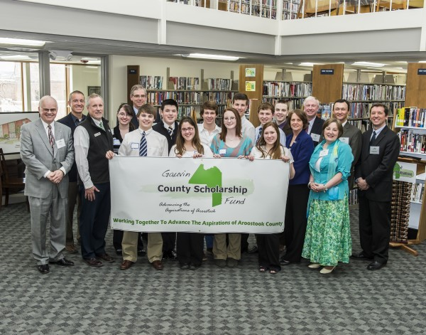 Ray (far left) and Sandy (right foreground) Gauvin flank students holding a banner celebrating the launch of the Aroostook Aspirations Initiative at the Turner Memorial Library in Presque Isle in April 2013.
