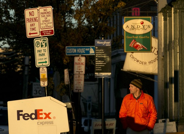The last rays of sun illuminate a pedestrian and signs on Commercial Street, Wednesday afternoon, Nov. 20, 2013, in Portland, Maine.