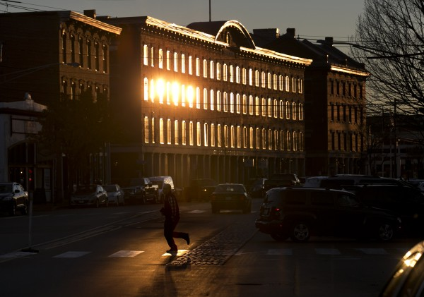 A pedestrian hurries across Commercial Street where the setting sun reflects off the Thomas Block building, Monday, Nov. 18, 2013, in Portland, Maine.