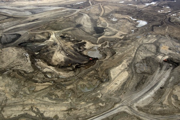 Oil is mined at a Syncrude Canada Ltd. mining site near Fort McMurray, Alberta. Canada's biggest energy companies are trailing global peers in reporting environmental performance as scrutiny of the oil sands intensifies.