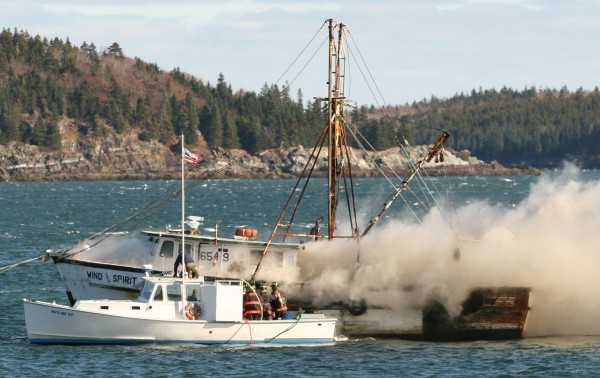 Bar Harbor firefighters on a lobster boat respond to a fire on a larger fishing vessel moored in the local harbor Wednesday morning. The larger boat, Wind And Spirit, suffered extensive damage in the blaze but did not sink, according to the Coast Guard.