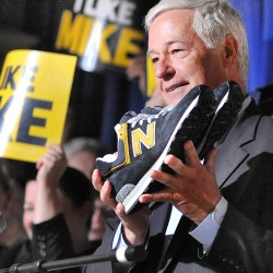Rep. Mike Michaud holds up a pair of New Balance sneakers that he said he would be wearing during his campaign during his official announcement of his intention to run for governor of Maine at the Franco-American Heritage Center in Lewiston recently