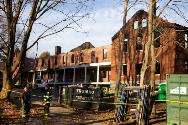 On Monday, Portland firefighters re-hang caution tape around the site of a Saturday fire which destroyed a hotel under construction on Great Diamond Island.