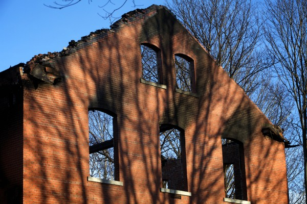 Brick walls and chimneys are all that remain Monday after a fire destroyed a hotel under development on Great Diamond Island in Casco Bay on Saturday.