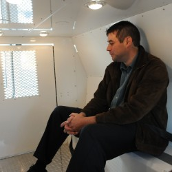 Scott Mathieu of Oxford Networks rides to the Muscular Dystrophy Association Lock Up in the back of the Bangor police van. Mathieu and others got courtesy rides to the Sea Dog in Bangor where they were finger printed, and had to sit in front of laptops and tablets making calls and email pleas to friends and business associates to donate funds on their behalf.