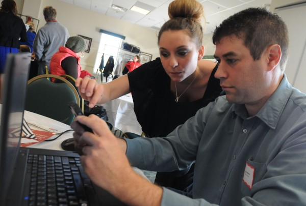 Scott Mathieu of Oxford Networks gets help from Brittni Wishart, an administrative assistant with the Muscular Dystrophy Association, as Mathieu sets up the web page he will use to raise funds for Muscular Dystrophy Association at the Sea Dog in Bangor on Wednesday.
