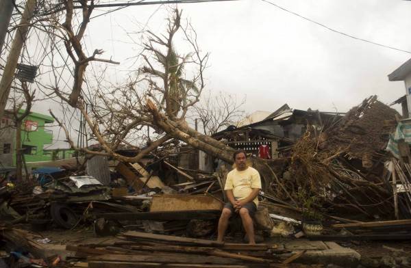 A resident sits on debris in typhoon-hit Leyte Province, Nov. 12, 2013. The United Nations said it had released $25 million in emergency funds to pay for emergency shelter materials and household items, and for assistance with the provision of emergency health services, safe water supplies and sanitation facilities. It's launching an appeal for more aid.