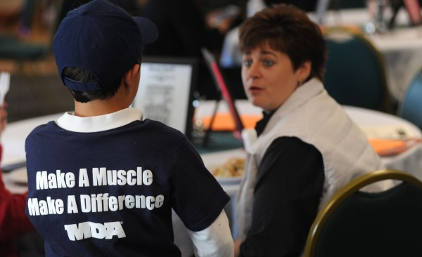 Muscular Dystrophy  ambassador Jared Conant talks with Maine Savings employee Sue Mogan as she raises funds for the Muscular Dystrophy Association during Wednesday's Lock Up at the Sea Dog in Bangor.