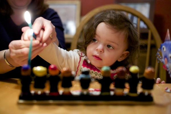 Gabrielle Matlins, 2, lights a menorah with the help of her mother, Paula, on the first night of Hanukkah Wednesday evening at their home in Bangor.