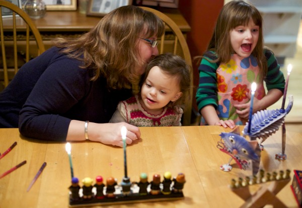 From left, Paula Matlins, kisses her daughter Gabrielle, 2, after lighting the menorah with Hannah, 4, during the first night of Hanukkah. The Matlins talk about how they're handling the confluence of Hanukkah and Thanksgiving this year as the start of Hanukkah is the day before Thanksgiving.