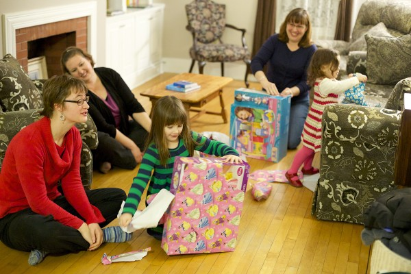 From left, Emma Hennessy and Terrie Hennessy watch as Hannah Matlins, 4, opens a gift on the first night of Hanukkah at the Matlins' home in Bangor Wednesday evening. Paula  Matlins, second from right, also helped her daughter Gabrielle, 2, open her gift. The Matlins spoke about how they're handling the confluence of Hanukkah and Thanksgiving this year as the start of Hanukkah is the day before Thanksgiving.
