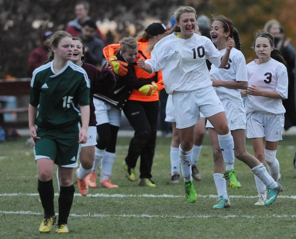 Members of the Orono girls soccer team celebrate their 2-1 double overtime victory while Fort Kent's Kendra Raymond (left) walks away in Orono on Wednesday during the Eastern Maine Class C championship.