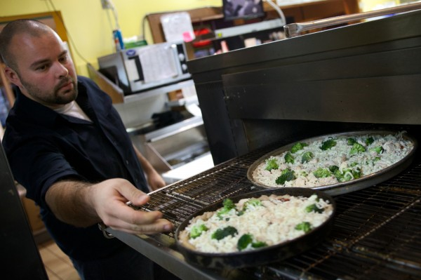 "Jason Cote, general manager at the Portland House of Pizza, puts two pies in the oven Tuesday. ""The day before Thanksgiving is always a nice, busy day for us,"" he said."