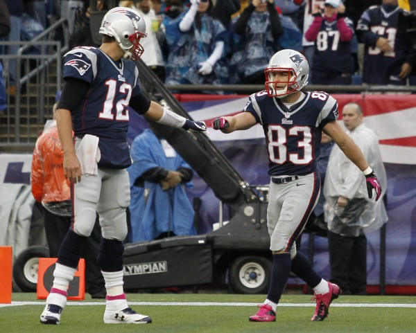 New England Patriots quarterback Tom Brady (L) celebrates with Patriots wide receiver Wes Welker (R) after Welker scored a touchdown against the Denver Broncos during the first quarter of their NFL football game in Foxborough, Massachusetts Oct. 7, 2012.