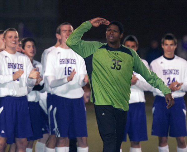 Hampden Academy goalkeeper Isaiah Bess salutes the Hampden fans as he is recognized during the awards ceremony after Hampden defeated Lewiston for the Eastern Maine Class A soccer championship in Hampden on Wednesday.
