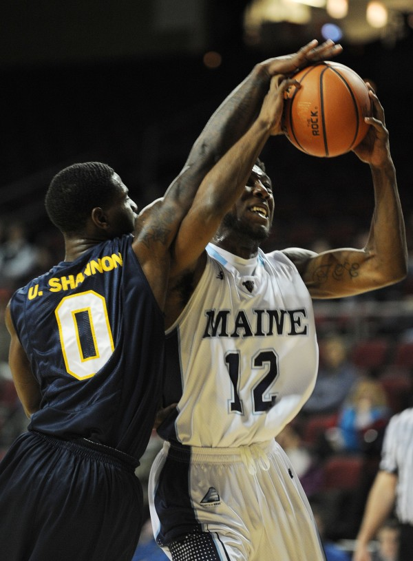 UMaine's Xavier Pollard is fouled by Quinnipiac's Umar Shannon while shooting during first half action at the Cross Insurance Center in Bangor on Monday.