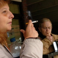 Crystal Fogleman (left) and Alice Goan (right), both of Bangor, smoke cigarettes as they wait for a bus in downtown Bangor in 2011.
