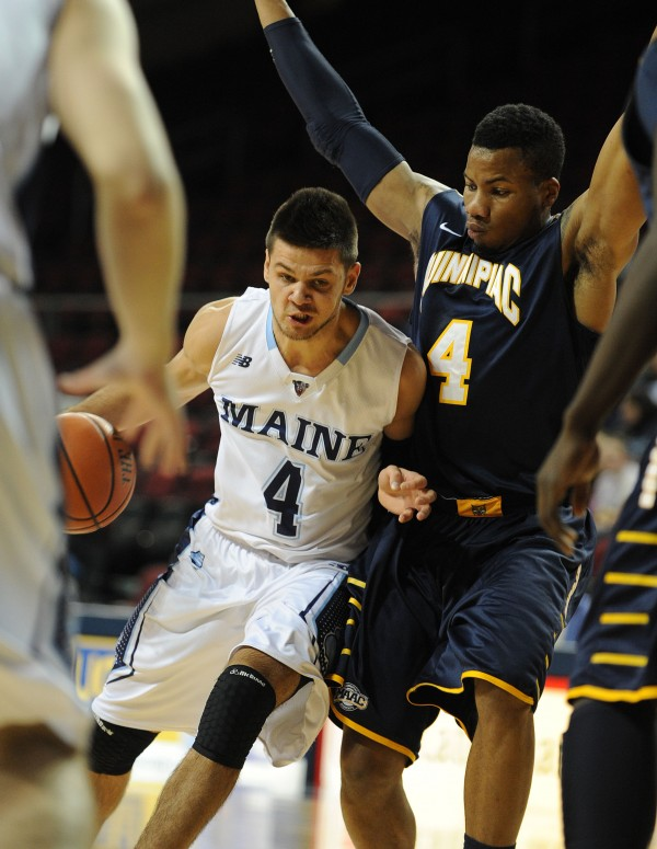 UMaine's Marko Pirovic dribbles through heavy traffic, including Quinnipiac's Ike Azotam, during first half action at the Cross Insurance Center in Bangor on Monday.