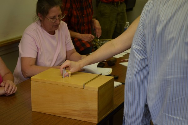 A resident places a vote in the ballot box at the Charleston Community Center in June.  The town voted to enact a 180-day moratorium on any east-west corridor development.